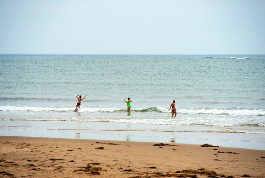 Visitors to Conrod's Beach play in the waves on Monday, July 12, 2021. Tropical Storm Elsa left behind conditions for powerful riptides. RCMP were called twice to the beach on Sunday for calls of swimmers caught in the riptide.