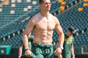 Edmonton Elks quarterback Trevor Harris loses a layer as the temperature topped 30 C at Commonwealth Stadium while training camp opened Saturday, July 10, 2021.