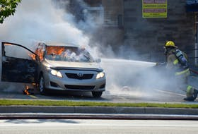 A firefighter attempts to put out a vehicle fire in the parking lot of the Royal Canadian Legion Branch 12 in Sydney on Tuesday. No injuries were reported in the fire.