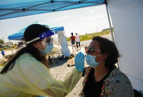 FOR NEWS STANDALONE: An emergency support aide, conducts a swab test for COVID-19, at a Public Health Mobile Testing site,  near the boardwalk at McCormacks Beach Provincial Park near Fishermen's Cove in Eastern Passage Tuesday July 13, 2021. - Tim Krochak
