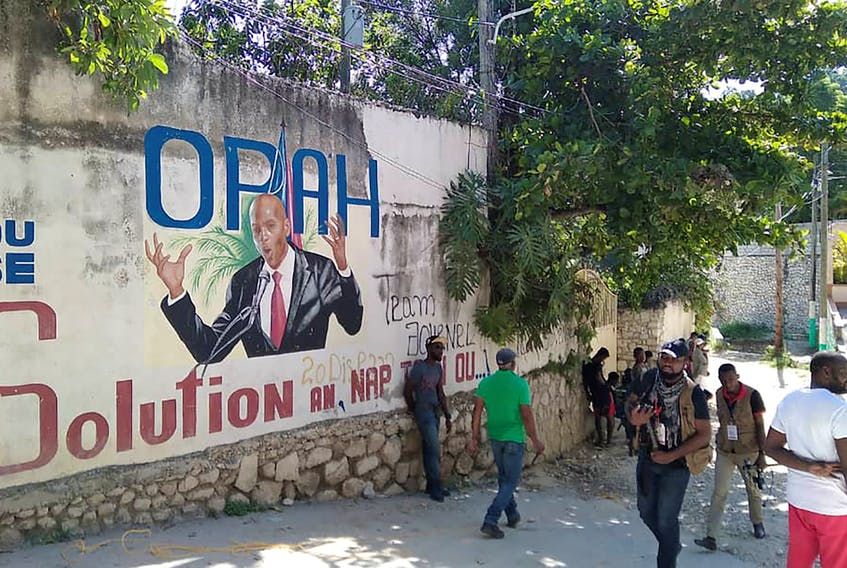 People walk past a wall with a mural depicting Haiti's President Jovenel Moise, after he was shot dead by unidentified attackers in his private residence, in Port-au-Prince, Haiti, July 7.