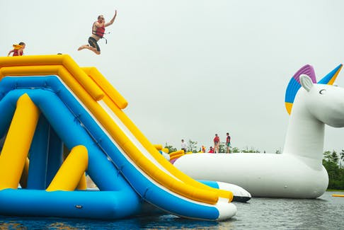 Dave Wolpin, co-owner of Splashifax launches down a slide during a friends and family event at the new inflatable water park in Hammonds Plains on Thursday, July 15, 2021. Splashifax opens to the public Friday, July 16, 2021.