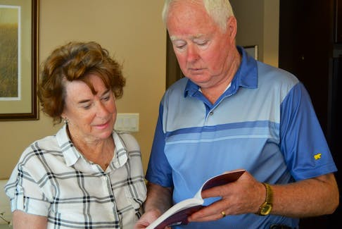 Ernie MacAulay, right, and his wife, Ruthann, look through his first book, a non-fiction story about the 1951 murder of his aunt, Mary Ann MacKinnon.