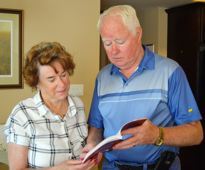 Ernie MacAulay, right, and his wife, Ruthann, look through his first book, a non-fiction story about the 1951 murder of his aunt, Mary Ann MacKinnon. - Dave Stewart