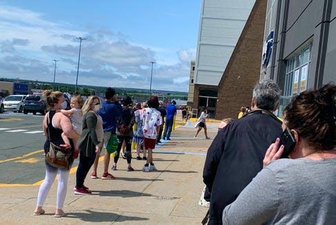 People were lined up outside the entrance to an Eastern Health COVID-19 vaccination clinic at the Village Shopping Centre in St. John' at lunchtime Friday. Eastern Health says a computer glitch led to delays in administration of vaccine doses. — Rosie Mullaley/SaltWire Network