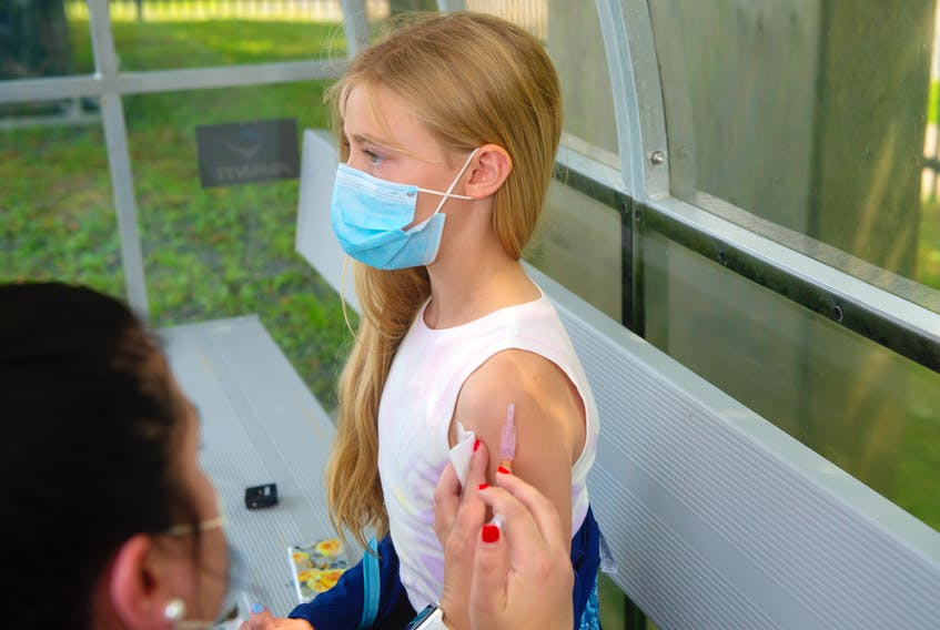 Annie Johns, 12, gets her first vaccine shot at a clinic on the Wanderers Grounds on Friday, July 16, 2021. The clinic was open to members of several local soccer clubs and adult leagues. The clinic continues on Saturday.