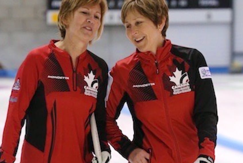 Representing Canada, Shelley MacNutt, left, and Colleen Pinkney are seen on the ice in Scotland in 2014 during the women's world curling championship.