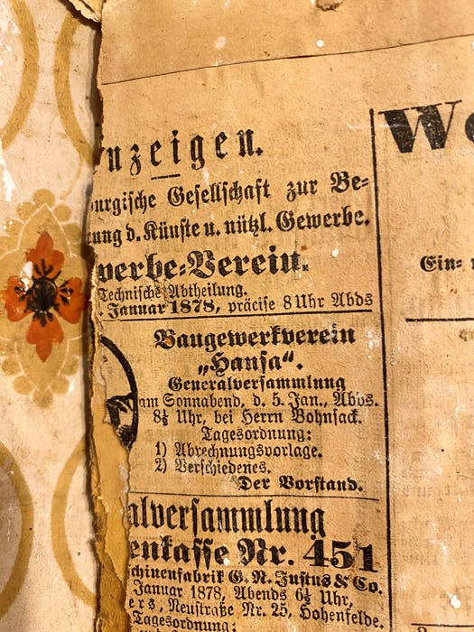 Newsprint from an issue of a newspaper published in Hamburg, Germany, in January of 1878 is glued to an interior wall.