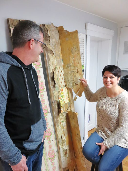 Owner Sharilee Anderson and friend, James Osborne, turning back seasoned wallpaper layers to uncover old newsprint.