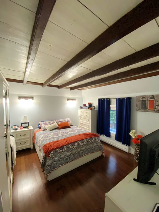 The attic wide-plank flooring and beams add a 19th-century feature to the ceiling of the main bedroom.