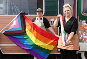 Christine Dickey, left, and Paige Heart were disappointed to find on July 16 that someone had cut down the Pride flag flying from their Holy Fox food truck in Cornwall. By 3 p.m., though, Pride P.E.I. had brought them a new flag.