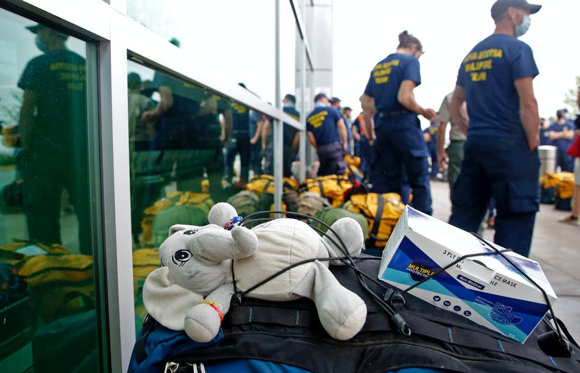A stuffed elephant is fixed to the bag of Nova Scotian firefighter Jamie Brown, right, as he and other firefighters prepare for deployments in Manitoba and Ontario to fight wildfires, at Halifax Stanfield International Airport on Friday, July 16, 2021. The plushie was a gift from his daughter Casey, 11, who gave it to him before his first out-of-province mission when she was four. Brown has deployed every year since with it. - Tim  Krochak