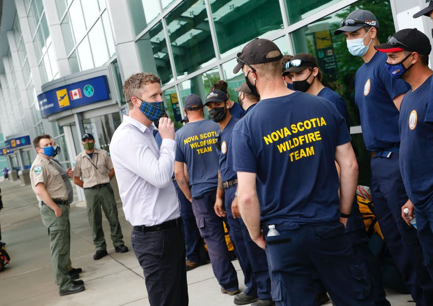 Premier Iain Rankin chats with a group of provincial firefighters as they prepare for deployments in Manitoba and Ontario to fight wildfires. - Tim  Krochak