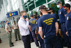 Premier Iain Rankin chats with a group of provincial firefighters as they prepare for deployments in Manitoba and Ontario to fight wildfires at Halifax Stanfield International Airport Friday July 16, 2021.