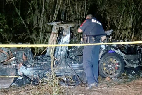 The remains of a Tesla vehicle are seen after it crashed in The Woodlands, Texas on April 17, 2021, in this still image from video obtained via social media. Investigators believe there was no one in the driver's seat of the vehicle, which was equipped with an Autopilot system, at the time of the fatal crash. SCOTT J. ENGLE via REUTERS/File Photo