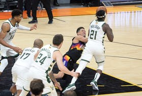 Milwaukee Bucks guard Jrue Holiday steals the ball form Phoenix Suns guard Devin Booker during Game 5.