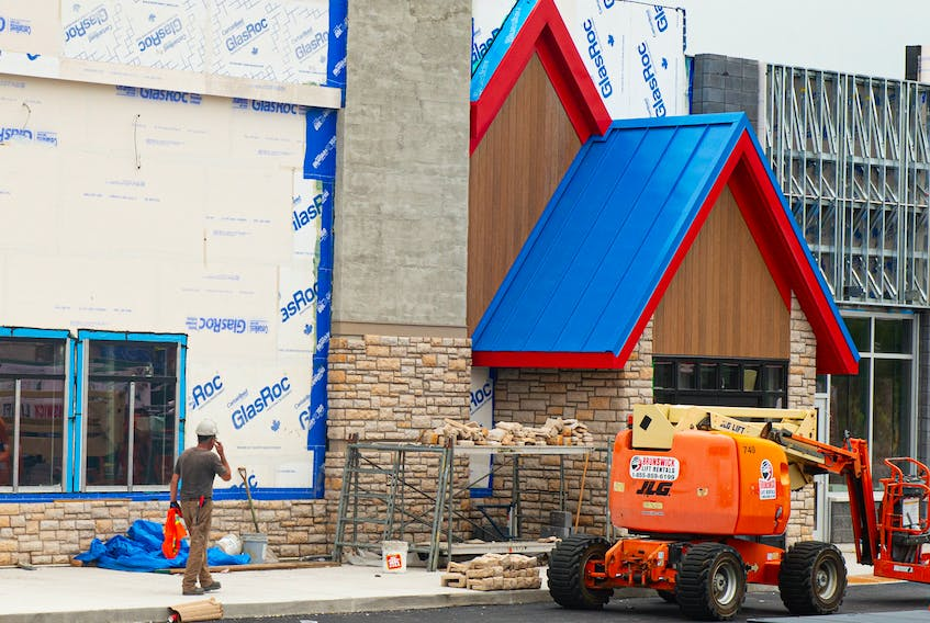 A construction worker walks past the building that will house the new IHOP in Bedford on Monday, July 19, 2021.