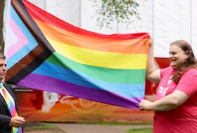 Pride Secretary Andrea MacPherson, right, holds up the Progress flag outside the Coles Building in Charlottetown, which is being raised for Pride Week. Premier Dennis King, left, and several MLAs were also present.