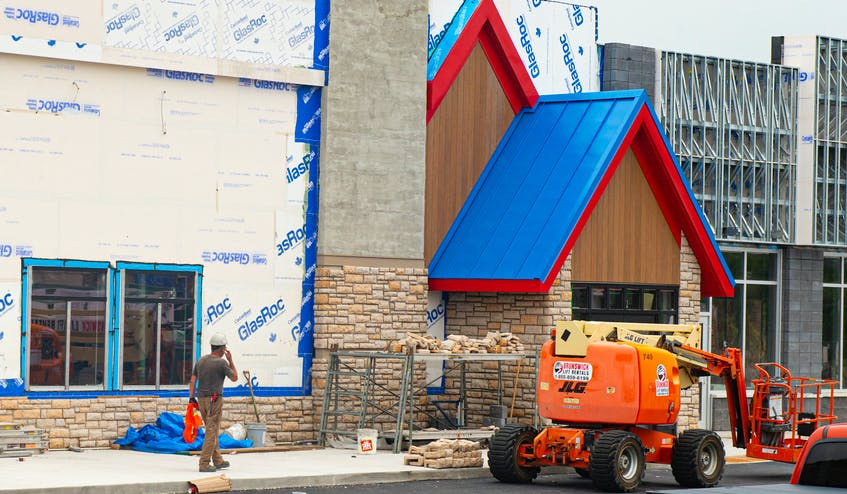 A construction worker walks past the building that will house the new IHOP in Bedford on Monday. - Ryan Taplin