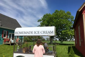 Ken Meister serves some ice cream from the Holman's Ice Cream cart making its first tour this summer. Meister had hoped to have the cart operating last summer, but the pandemic derailed plans.