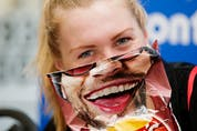 Canada's Joanna Brown goofs around with a potato chip bag while taking part in an ITU World Triathlon Edmonton press conference in Hawrelak Park in Edmonton on July 27, 2017.