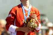 Simon Whitfield of Kingston, Ont., raises his head to the heavens as he stands on the podium with his gold medal and a bouquet of flowers in Sydney 2000 after winning the triathlon event.