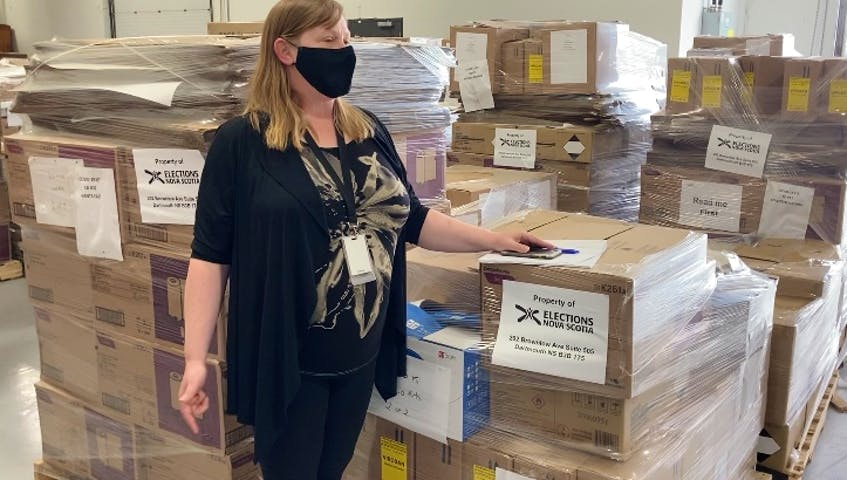Naomi Shelton, director of communications and policy for Elections Nova Scotia, stands in front of election packages ready to be delivered to the 55 provincial ridings in the lead up to the election call. - Francis Campbell