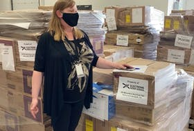Naomi Shelton, director of communications and policy for Elections Nova Scotia, stands in front of election packages ready to be delivered to the 55 provincial ridings last week before the election was called.