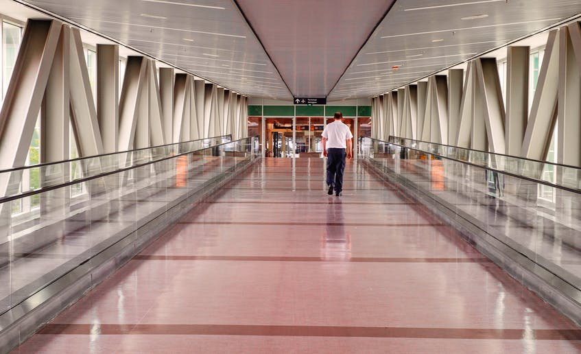 A Halifax Stanfield Airport employee walks through a quiet pedway on Tuesday.  Ryan Taplin - The Chronicle Herald
