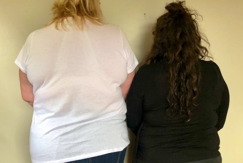 A middle-aged trans woman and a middle-aged cis woman standing beside each other for comparison of size. For a transgender woman to be approved for breast surgery by Nova Scotia health coverage, they are judged on need based on the Tanner Scale, which uses five levels to explain body development on cis female and male anatomy from puberty to maturity. CONTRIBUTED