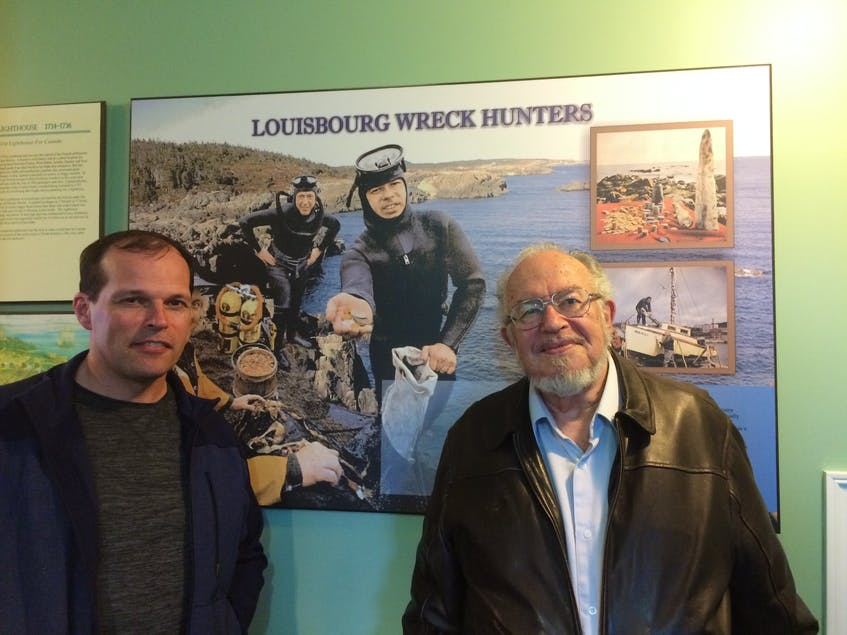 Jason Storm, left, poses with his father, the late Alex Storm, the famed Nova Scotia shipwreck hunter, in front of a photo showing one of his expeditions near Louisbourg. CONTRIBUTED