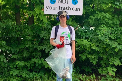 Justin Greeno standing next to his poster with his favourite saying, 'The World is NOT Your Trash Can.' Contributed