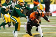 Edmonton Elks defensive end Mathieu Betts (9) helps haul down BC Lions quarterback Danny O'Brien (2) for a sack at Commonwealth Stadium in Edmonton on Oct. 12, 2019.