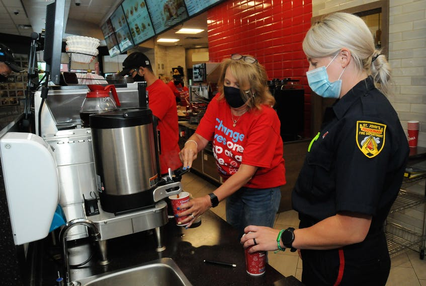 """Pegged as """"Your Opportunity to Open Doors for Youth in the Community,"""" July 21 was the national Tim Horton's Camp Day across the province and Canada. All the Tim Hortons restaurant owners donated 100 per cent of the proceeds from hot and iced coffee sales to send youth ages 12-16 to one of the six camps across Canada. Each year, community groups and people from various working backgrounds, volunteer their time to assist Tim Horton's staff team members at various restaurants on Camp Day. At the Tim Horton's outlet on Harvey Road, St. John's Regional Fire Department fire fighter Stephanie McGrath of the Central Fire Station's Engine 1 pumper crew assists Tim's co-owner Beverley Burt, in preparing a customer's order. At far left is Tim's team member Basit Abdul. McGrath's time was short-lived though as she and her crew had to leave for a minor call in the city's east end. In Atlantic Canada, Camp goers can attend the Tim's Camp in Tatamagouche, N.S. to participate in traditional camp activities like canoeing, high ropes and overnight wilderness expeditions, as well as academic workshops like how to create a budget, apply for post-secondary scholarships and build a career path. The summer program also helps youth develop life skills and coping strategies to help achieve success in school and work, and encourages them to give back to their communities."""