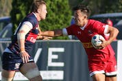 Canada's Nathan Hiramaya (10) straight-arms a USA player during International rugby match action between Canada (red) and USA (blue) at Twin Elm Rugby Park in Nepean (Ottawa) this afternoon, Saturday, August 22, 2015. Canada vs. USA. International Rugby. Twin Elm Rugby Park.