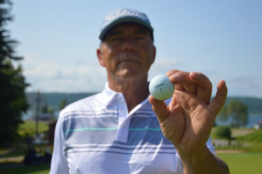 Martin Burke holds the ball in which he carded an albatross with during a round of golf at The Lakes Golf Club last month in Ben Eoin. The Sydney golfer has been a member at the course since it opened. JEREMY FRASER/CAPE BRETON POST