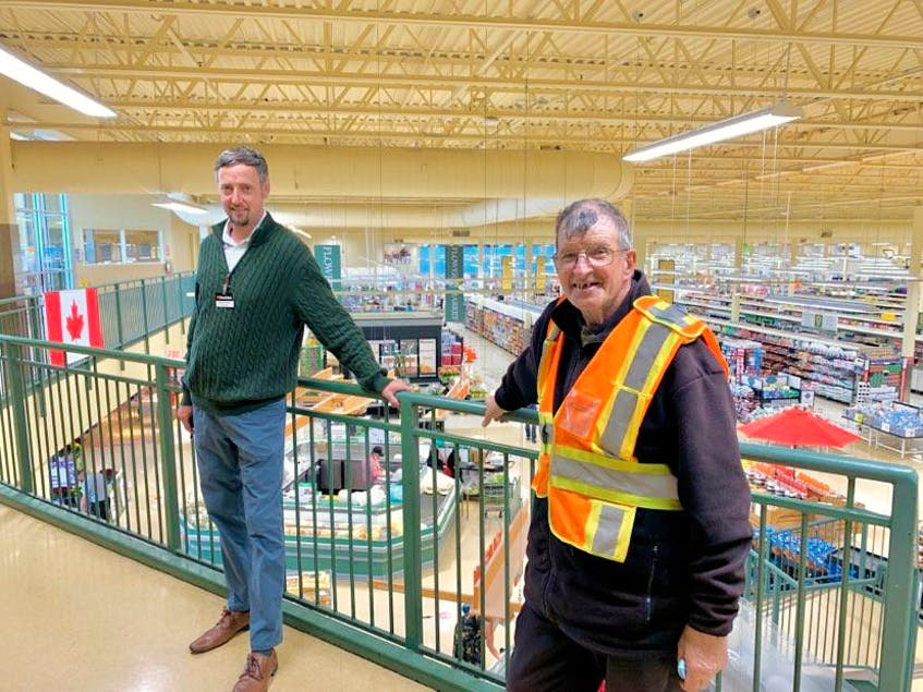 Andrew Norris (left), manager of Dominion supermarket on Blackmarsh Road in St. John's, said he and the many employees at the company will be sad to see Marty Heffernan (right) go. Heffernan, who turned 65 July 21 will work his final shift July 23. — Rosie Mullaley