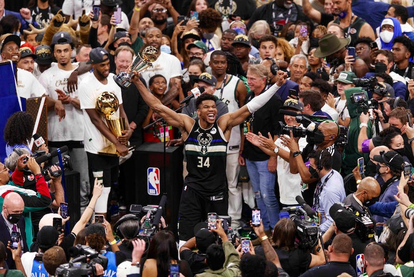 Milwaukee Bucks forward Giannis Antetokounmpo (34) celebrates with the NBA Finals MVP Trophy following the game against the Phoenix Suns following game six of the 2021 NBA Finals at Fiserv Forum.