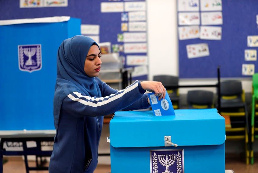 An Arab-Israeli woman casts her ballot as she votes in Israel's national election at a polling station in  Tamra, Israel, in March.- REUTERS/Ammar Awad