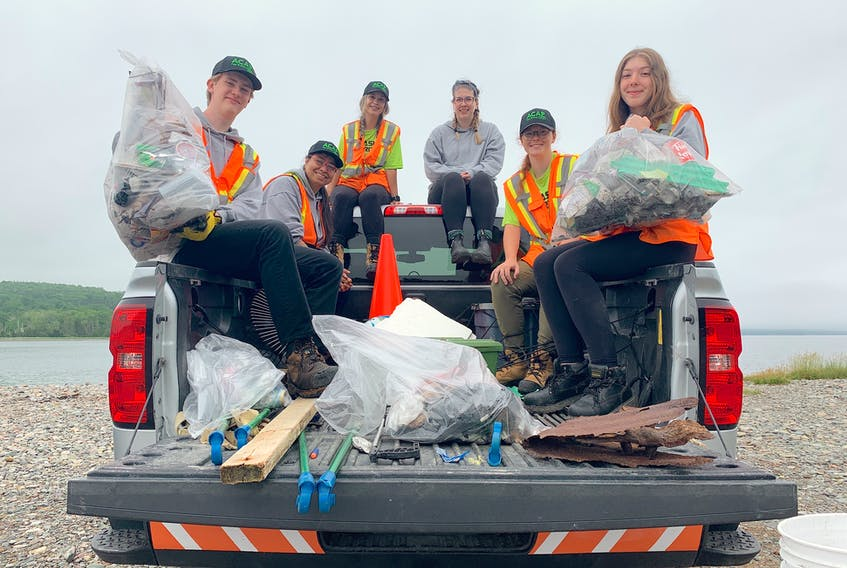 ACAP Cape Breton's Trashformers team holds up some of the litter they picked up during a recent cleanup at the sandbar in East Bay. From left are Jack Gillespie, Pritika Dadich, Emma Wrathall, Ally Chant, Eve Bunbury and Kaylee Petite. So far, the environmental non-profit reports they've encountered an unusual number of urine-filled bottles, soiled adult diapers and used feminine hygiene products. Chris Connors/Cape Breton Post