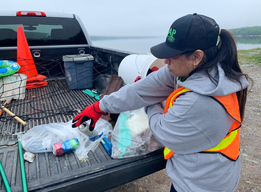 Pritika Dadich puts some empty cans of alcoholic beverages she picked up at the East Bay sandbar into a bag. Unlike past years when ACAP Cape Breton's Trashformers teams mainly collected discarded water and soda bottles, this year has been vastly different. Chris Connors/Cape Breton Post