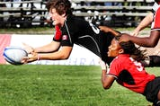 Britt Benn of Team Canada (in Black) throws the ball as she's tackled by Team Trinidad and Tobago (in Red), during the North American Caribbean Rugby Association qualifying tournament for Moscos Cup, held at Twin Elm Rugby Park, in Ottawa, on, on August 27, 2012. Team Canada won 46-0.