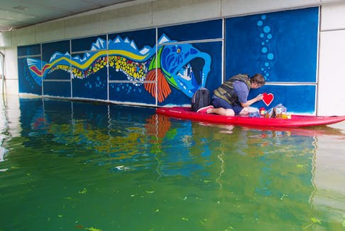 Calgary artist Brad Hays paints from a stand-up paddle board as he nears completion on a unique mural under the bridge crossing the Bowness Lagoon on Wednesday, July 7, 2021. The logo draws on an historical news story from 1942 when a massive ling fish that was nicknamed Ogopogo startled visitors at Bowness Lagoon. The fish was eventually caught and killed by parks staff.  Gavin Young/Postmedia