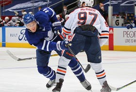 Connor McDavid (97) of the Edmonton Oilers holds up Zach Hyman (11) of the Toronto Maple Leafs at Scotiabank Arena on March 29, 2021, in Toronto.