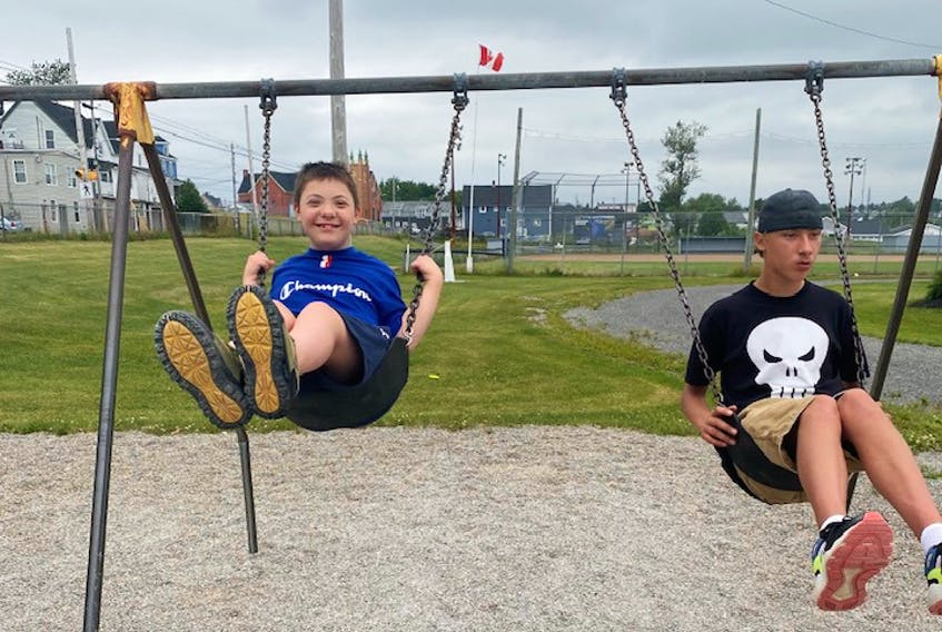 Charles Levatte, left, and Steven Parris have some fun on the swings during an ADAPT Recreation camp in Sydney.