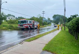 A telephone pole on Coxheath Road is shown smoking as members of the Coxheath Volunteer Fire Department asses the incident Thursday afternoon. The fire is believed to have caused a power outrage stretching as far as Grand Narrows.