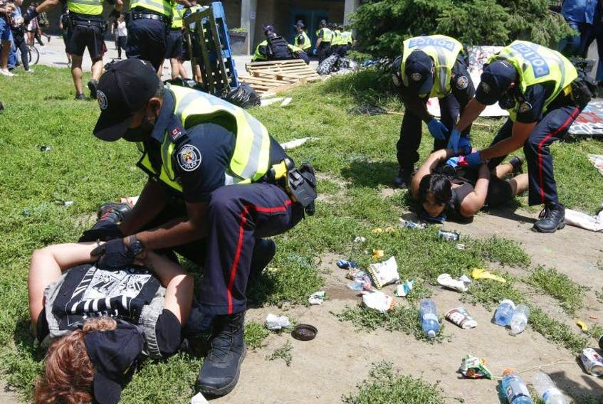 Toronto Police make arrests as city crews moved in to clear a homeless encampment on the west side of Lamport Stadium around 1:30 p.m. on Wednesday July 21, 2021.
