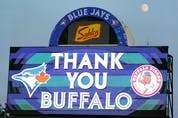 The moon rises over the message to the Buffalo fans during the game between the Toronto Blue Jays and the Boston Red Sox at Sahlen Field on July 21, 2021 in Buffalo. KEVIN HOFFMAN/GETTY IMAGES