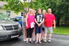 Resume in hand, job-hunter Lori Delaney is ready to take the family minivan and head back to work after 21 years of raising her family with her husband, Keith Delaney. Her children, from left, Hannah, Abby, Riley, and Casey, as well as daughter Mia - who is not in the photograph - support their mother.