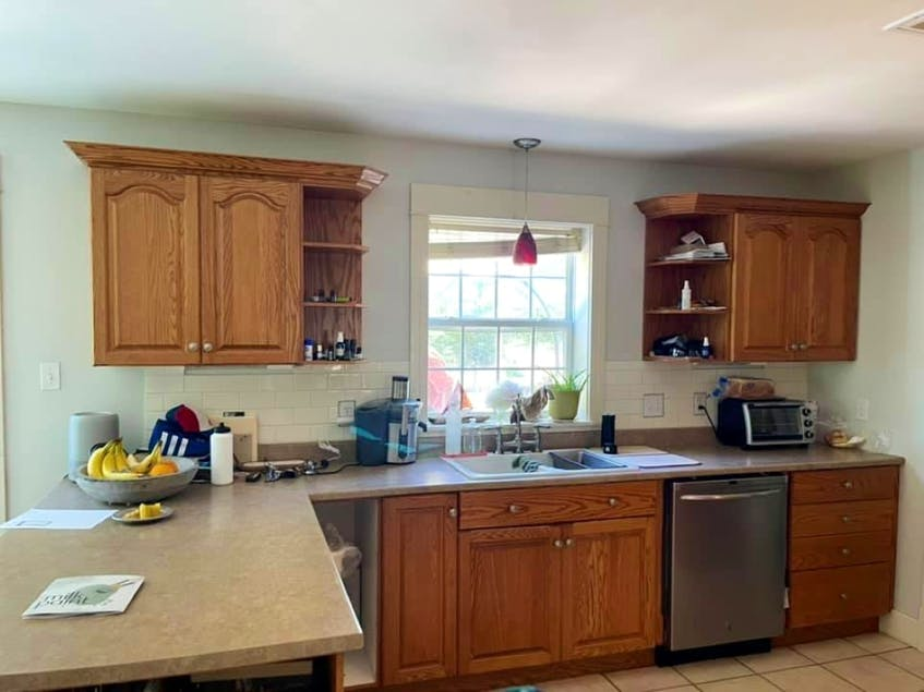 Meegan Lovett removed the dated cupboards near her window and replaced them with open shelving, then painted her older kitchen cabinets a bright white.